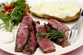Closeup on slices of grilled gourmet wagyu rib-eye steak served with horseradish sauce, a baked pota