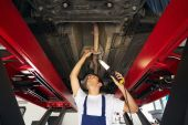 pic of car repair shop  - mechanic standing under car engine and holding lamp - JPG