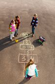 stock photo of hopscotch  - Group of kids jumping on the Hopscotch game drawn on the asphalt after school wearing autumn clothes - JPG