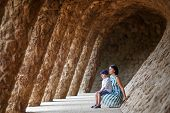 Young mother and her son walking Park Guell