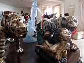 Tigers, Dolphins, And A Mermaid Sculputres Display On A Table At Auction