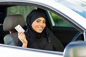 cheerful muslim woman showing a driving license she just got