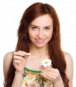 Young woman is tearing up daisy petals, isolated over white