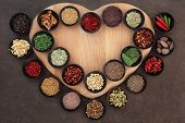 Herb and spice collection on a heart shaped board in wooden bowls.