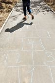 Girl Hops In Hopscotch On Urban Alley