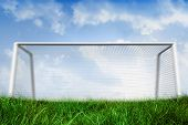 Digitally generated goalpost on grass under blue sky