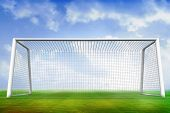 Digitally generated football pitch and goal under blue sky