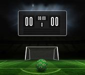 Football in brazilian colours and scoreboard against football pitch and goal under spotlights