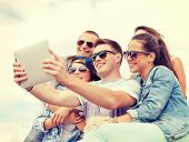 summer holidays, teenage and technology concept - group of smiling teenagers in sunglasses taking picture with tablet pc