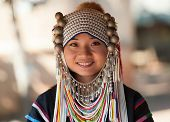 CHIANG RAI, THAILAND - DEC 4, 2013: Unidentified Akha girl in traditional clothes and silver jewelery in akha hill tribe minority village near Chiang Mai. Young asian woman with smile on face