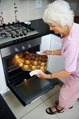 A happy grandmother taking muffins out of the oven