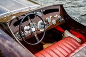 stock photo of steers  - A view of the steering wheel and dashboard of a wooden motor boat - JPG