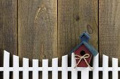 Birdhouse hanging on white picket fence