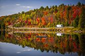 Fall forest with colorful autumn leaves and highway 60 reflecting in Lake of Two Rivers.  Algonquin