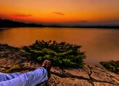 Relaxing Under an Orange Sunset Over a Calm Lake