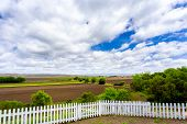 White Picket Fence, Farmland, And Clouds