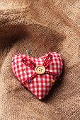 Fabric heart with color pins on sackcloth background