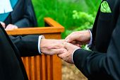 foto of gay wedding  - A man putting a ring on another man - JPG