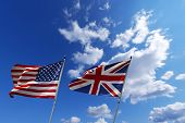 stock photo of flag confederate  - English and American flag waving in the wind on blue sky with clouds  - JPG