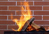 stock photo of brazier  - burning wood in a brazier on the brick wall background - JPG