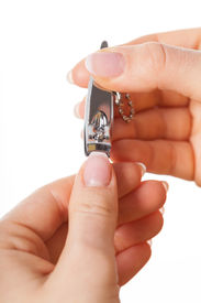 stock photo of nail-cutter  - Woman cutting nails by small silver nails cutter - JPG