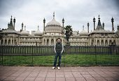 Young male tourist standing in front of the external facade of the historical Brighton Palace Pavilion with its ornate architecture and symmetrical design
