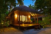 Beach bungalow at sunset - Maldives vacation background
