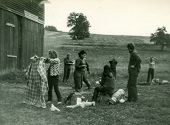 POLAND, CIRCA SIXTIES: Group of young hitchhikers with backpacks prepare a camping in farm, vintage photo