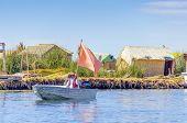 PUNO, PERU, MAY 5, 2014: Inhabitants of Uros Islands travel by boat between islands