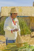 PUNO, PERU, MAY 5, 2014: Inhabitant of Uros Islands in traditional attire shows the local mode of using the reed for crafts and building