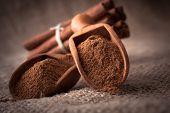 ground cinnamon spice powder in wooden spoon