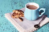 Cup of coffee with cookies and napkin on wooden table