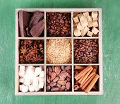 Wooden box with set of coffee and cocoa beans, sugar cubes, dark chocolate, cinnamon and anise over wooden background