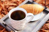 Cup of tasty hot drink and fresh croissant on tray, on autumn leaves background