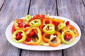 Sliced pepper on oval plate on wooden background