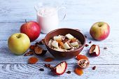 Bowl of oatmeal, walnuts, dried apricots, apples and yogurt on blue wooden background