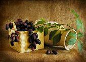 Uvas en una cesta y un florero, una naturaleza muerta.