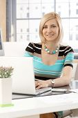 Portrait of casual blonde caucasian secretary working with laptop computer in brightly lit office, smiling at camera.