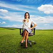 frowning businesswoman sitting on the chair and pointing at camera. photo at outdoor