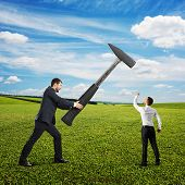 big businessman holding hammer, small businessman showing fist and screaming. photo at outdoor