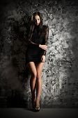 Fashion style portrait of young girl on grey rough wall background