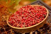 Dried wild rose hips in an artisan wooden bowl in autumn