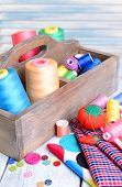 Sewing Accessories in wooden box on table on light blue background