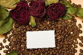 dry red roses and blank paper sheet on coffee seeds and wooden background