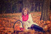 Beautiful young woman posing with pumpkin, apples