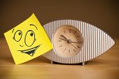 Drawn smiley face on a post-it note sticked on alarm clock