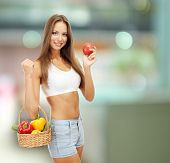Shopping concept. Beautiful young woman with vegetables in basket on shop background