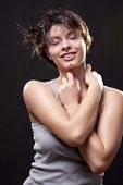 Wet young woman with a gray top.  Fine spray of water. Post production - without styling filters