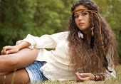 Beautiful hippie girl with rope in hair in the park