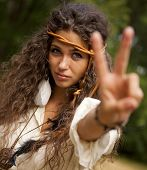 stock photo of hippy  - Beautiful hippie girl with rope in the park making the sign of peace - JPG